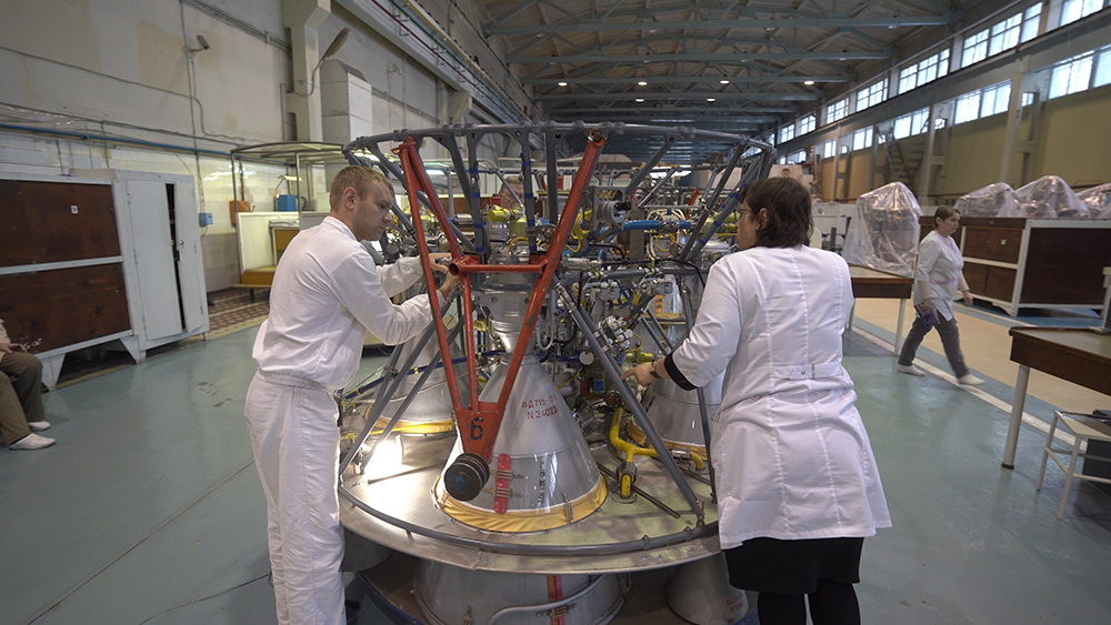 Male and female workers handling a rocket engine
